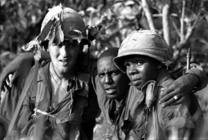 A wounded soldier is helped to a waiting helicopter by two of his comrades during Operation Attleboro near Near Tay Ninh, WSouth Vietnam, in November, 1966.