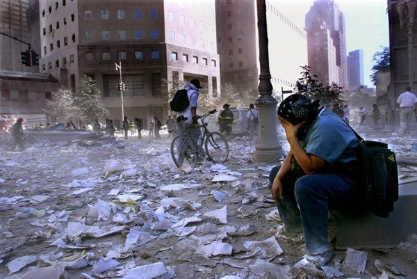 A man sits near the smoky remains of the fallen World Trade Center, taken on September 11th.